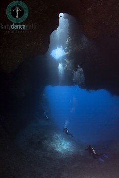 Palau, 2016, Blue Hole site, three divers exit the cavern in perfect symmetry.